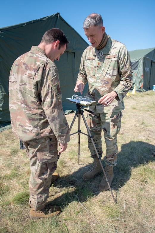 Maj. Kevin Eilers (right), bio-environmental engineer for the Kentucky Air National Guard's 123rd Contingency Response Group, demonstrates how to use a wet bulb globe temperature apparatus to Master Sgt. Peter Vicini during Operation Lone Oak at Volk Field, Wis., June 9, 2021. The apparatus takes temperature readings to determine work-rest cycles during certain weather conditions, which became crucial for safety during an unprecedented heat wave over the course of the exercise. (U.S. Air National Guard photo by Senior Master Sgt. Vicky Spesard)