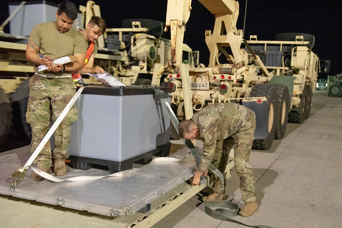 Aerial porters from the Kentucky Air National Guard's 123rd Contingency Response Group and movement specialists with the U.S. Army's 690th Rapid Port Opening Element from Fort Eustis, Va., secure cargo during a Joint Task Force-Port Opening exercise known as Operation Lone Oak at Volk Field, Wis., June 11, 2021. The objective of a JTF-PO is to establish a complete air logistics hub and surface distribution network. (U.S. Air National Guard photo by Senior Master Sgt. Vicky Spesard)