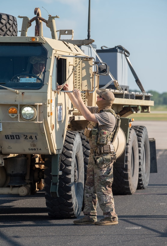 Staff Sgt. Chandler Hunter, a security forces specialist from the Kentucky Air National Guard's 123rd Contingency Response Group, checks a U.S. Army cargo carrier through the gate during a Joint Task Force-Port Opening exercise known as Operation Lone Oak at Volk Field, Wis., June 11, 2021. The cargo movement was part of everyday operations during the JFT-PO exercise, which combined the efforts of the CRG with the U.S. Army's 690th Rapid Port Opening Element from Fort Eustis, Va. The objective of a JTF-PO is to establish a complete air logistics hub and surface distribution network. (U.S. Air National Guard photo by Senior Master Sgt. Vicky Spesard)