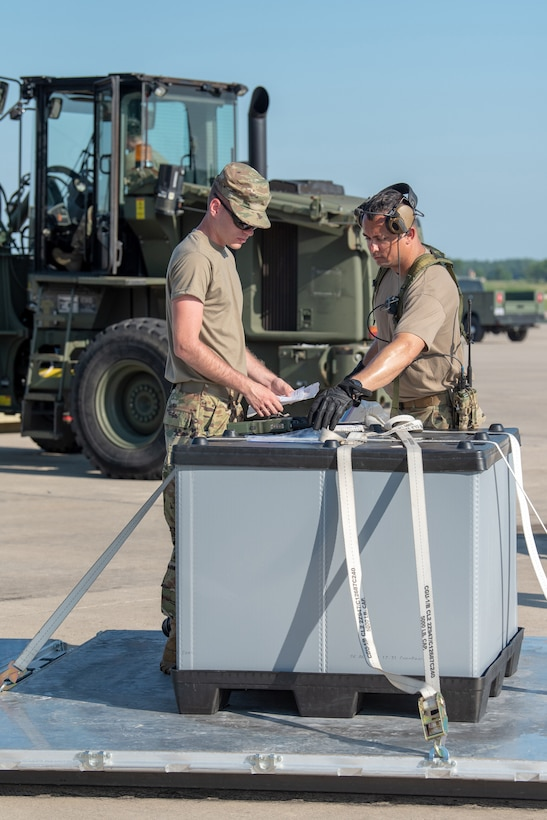 Staff Sgt. Jacob Land and Tech. Sgt. David Gomes, aerial porters from the Kentucky Air National Guard's 123rd Contingency Response Group, track cargo movements during a Joint Task Force-Port Opening exercise known as Operation Lone Oak at Volk Field, Wis., June 11, 2021. The movement was part of everyday operations during the JFT-PO exercise, which combined the efforts of the CRG with the U.S. Army's 690th Rapid Port Opening Element from Fort Eustis, Va. The objective of a JTF-PO is to establish a complete air logistics hub and surface distribution network. (U.S. Air National Guard photo by Senior Master Sgt. Vicky Spesard)