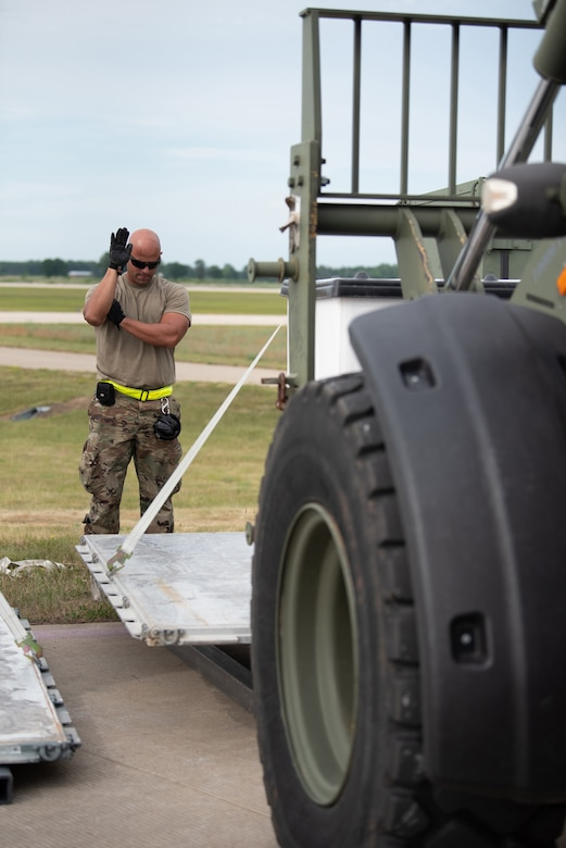 Senior Airman Ricardo Aguilera-Salas, an aerial porter from the Puerto Rico Air National Guard who was augmenting the Kentucky Air National Guard's 123rd Contingency Response Group, guides cargo during Operation Lone Oak at Volk Field, Wis., June 11, 2021. Aerial porters moved cargo 24 hours a day during the exercise. (U.S. Air National Guard photo by Senior Master Sgt. Vicky Spesard)