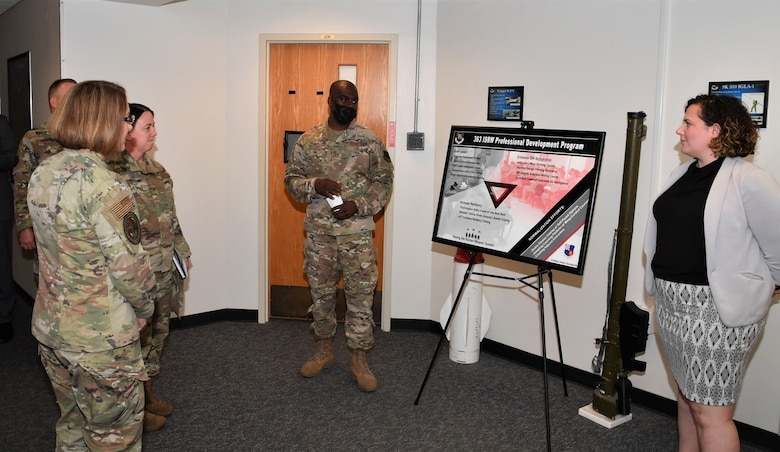 Several Airmen in uniform and one civilian stand in front a presentation board.