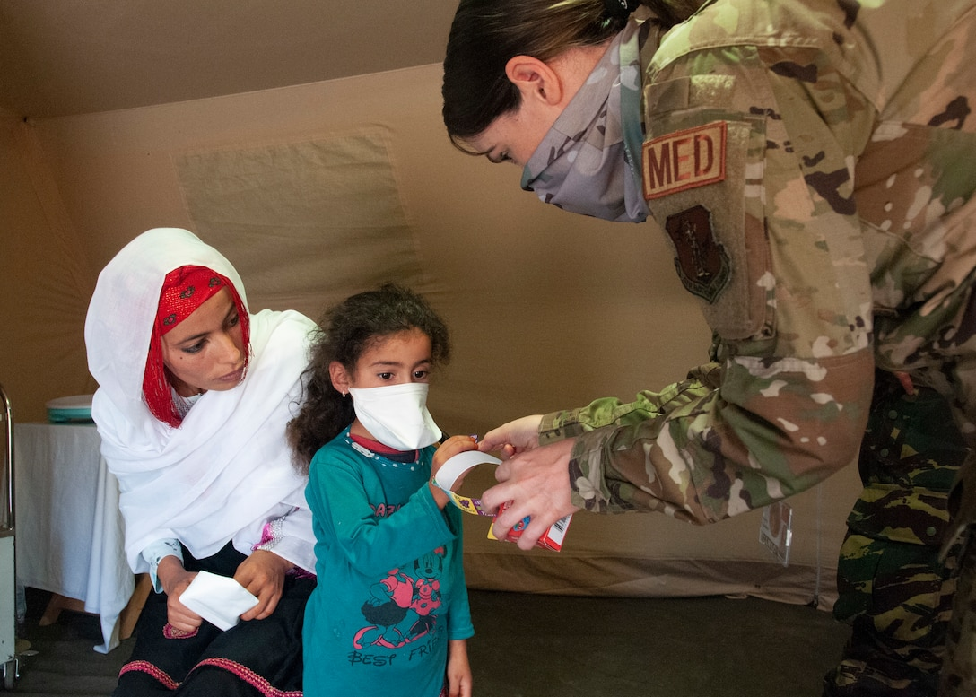 U.S. Air Force 1st Lt. Kimberly Hegeman, a nurse with the 151st Medical Group, gives a sticker to a child visiting the pediatric section of the military field hospital, June 7, 2021 in Tafraoute, Morocco during exercise African Lion 2021. The exercise is U.S. Africa Command's largest, premier, joint, annual exercise hosted by Morocco, Tunisia, and Senegal. AL21 is a multi-domain, null-component, and multinational exercise, which employs a full array of mission capabilities with the goal to strengthen interoperability among participants. (U.S. Air National Guard photo by Tech. Sgt. Annie Edwards)