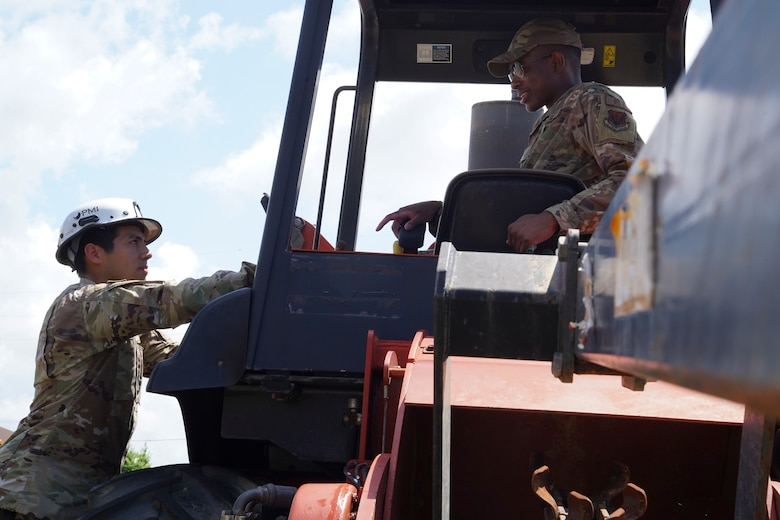 U.S. Air Force Senior Airman David Mirnada and Khari Harris, 85th Engineering Installation cable and antenna installers, check a tractor at Keesler Air Force Base, Mississippi, June 23, 2021. The 85th EIS is the only active duty command, control, communication-computer engineering and installation squadron in the Air Force. (U.S. Air Force photo by Senior Airman Spencer Tobler)