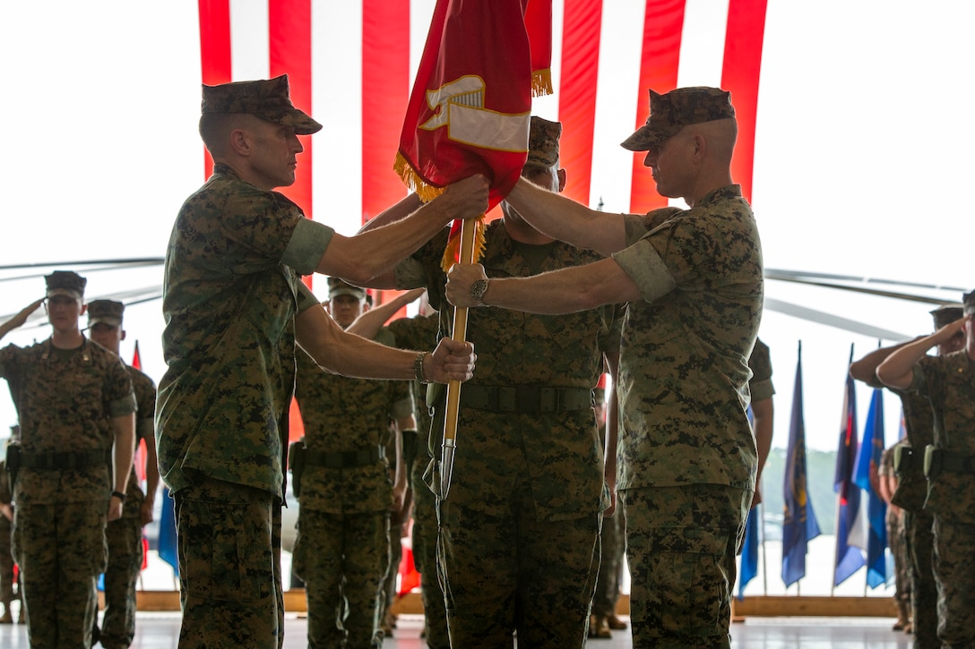 U.S. Marine Corps Col. Robert B. Finneran, right, passes the squadron colors to Col. Richard D. Joyce, left, during a change of command ceremony for Marine Aircraft Group (MAG) 29 at Marine Corps Air Station New River, North Carolina, June 10, 2021. The ceremony represented a transfer of responsibility and authority from Finneran to Joyce. MAG-29 is a subordinate unit of 2nd Marine Aircraft Wing (MAW), the aviation combat element of II Marine Expeditionary Force.     For the past two years, Finneran has served as commander of MAG-29, which is composed of eight rotary-wing squadrons manned by 2,900 Marines and Sailors. During that time, MAG-29 converted from its AH-1W helicopters to the upgraded AH-1Z model in both of its attack squadrons. The group deployed two detachment in support of Special Purpose Marine Air-Ground Task Force Southern Command, multiple deployments for training, multiple Weapons and Tactics Instructor courses and multiple Integrated Training Exercises ITX while still providing support to II Marine Expeditionary Force. His next assignment will be to Headquarters Marine Corps, Department of Aviation where he will serve as branch head for Air Warfare Systems – Assault Support.     Joyce has deployed numerous times to Iraq and Afghanistan, served as the commanding officer of an attack squadron, and as the Director of the Staff Group for Gen. Robert B. Neller, the 37th Commandant of the Marine Corps. He recently finished his assignment as the Director of Safety and Standardization of 2nd MAW. (U.S. Marine Corps photo by Cpl. Damaris Arias)
