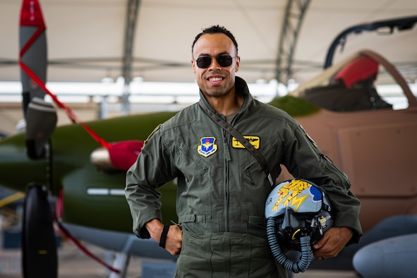 A photo of an Airman posing in front of an aircraft