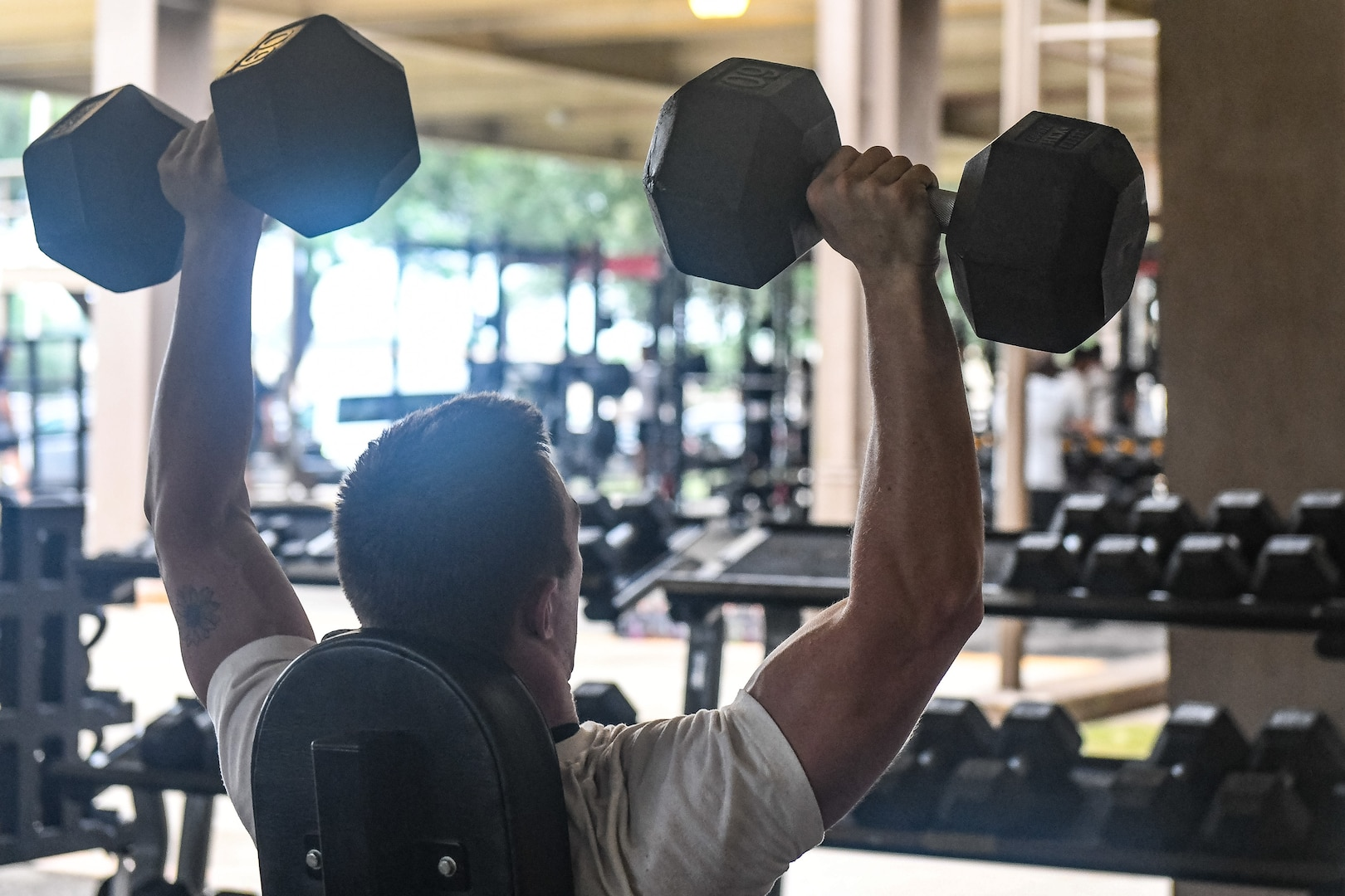 Training student lifting dumbbells over his head.