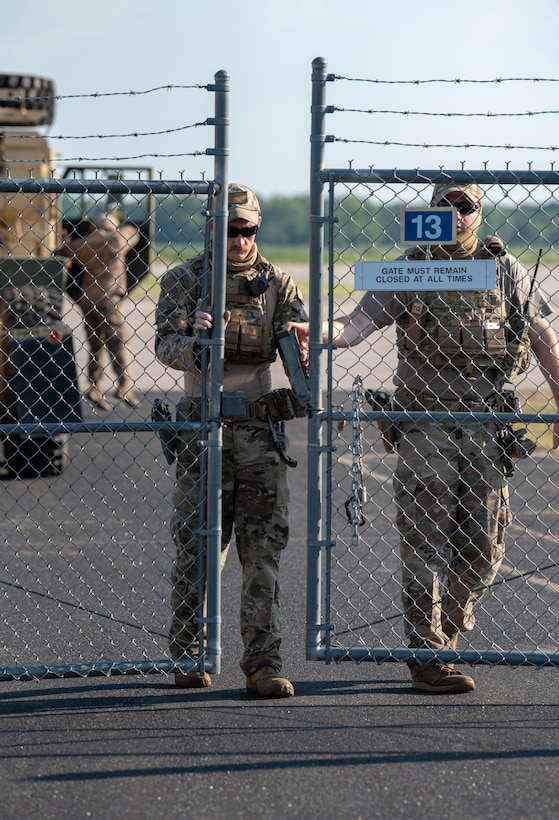 Senior Airman Tyler McCauley and Staff Sgt. Chandler Hunter, security forces specialists with the Kentucky Air National Guard's 123rd Contingency Response Group, secure the gate during a Joint Task Force-Port Opening exercise known as Operation Lone Oak at Volk Field, Wis., June 11, 2021. The objective of the JTF-PO is to establish a complete air logistics hub and surface distribution network. (U.S. Air National Guard photo by Senior Master Sgt. Vicky Spesard)