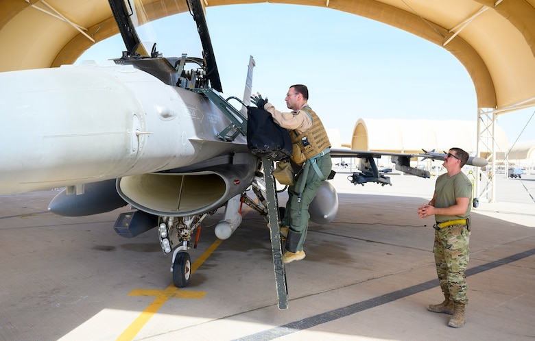 U.S. Air Force Brig. Gen. Robert Davis, 378th Air Expeditionary Wing commander, climbs into a U.S. Air Force F-16 Fighting Falcon, while U.S. Air Force Senior Airman Ryan West, 157th Expeditionary Fighter Generation Squadron F-16 crew chief, prepares to assist in initial flight preparations, Prince Sultan Air Base, Kingdom of Saudi Arabia, June 20, 2021. Davis, a trained fighter pilot, flew his first F-16 sortie with the 157th Expeditionary Fighter Squadron, currently deployed to PSAB to bolster defensive capabilities against potential threats in the region. (U.S. Air Force photo by Senior Airman Samuel Earick)