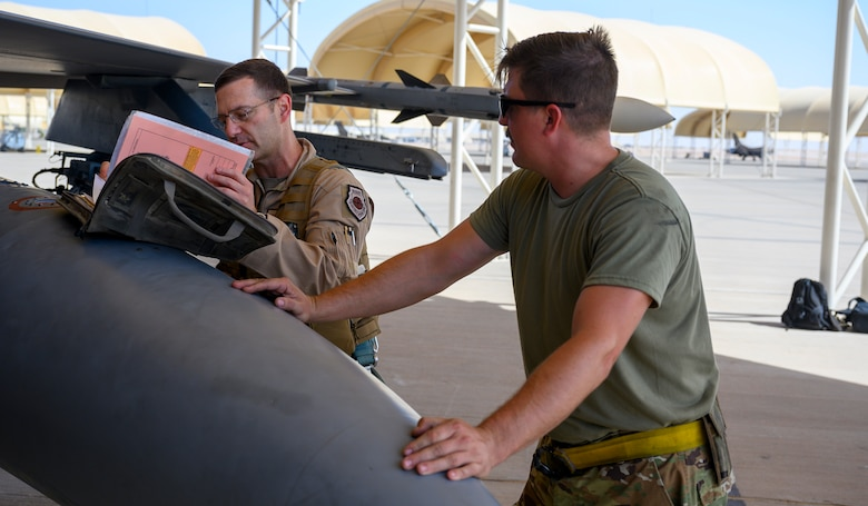 U.S. Air Force Brig. Gen. Robert Davis, 378th Air Expeditionary Wing commander, looks over aircraft documentation on a U.S. Air Force F-16 Fighting Falcon prior to his first flight on base while U.S. Air Force Senior Airman Ryan West, 157th Expeditionary Fighter Generation Squadron F-16 crew chief, stands ready to provide assistance, Prince Sultan Air Base, Kingdom of Saudi Arabia, June 20, 2021. Davis, a trained fighter pilot, flew a sortie with the 157th Expeditionary Fighter Squadron, currently deployed to PSAB to bolster defensive capabilities against potential threats in the region. (U.S. Air Force photo by Senior Airman Samuel Earick)