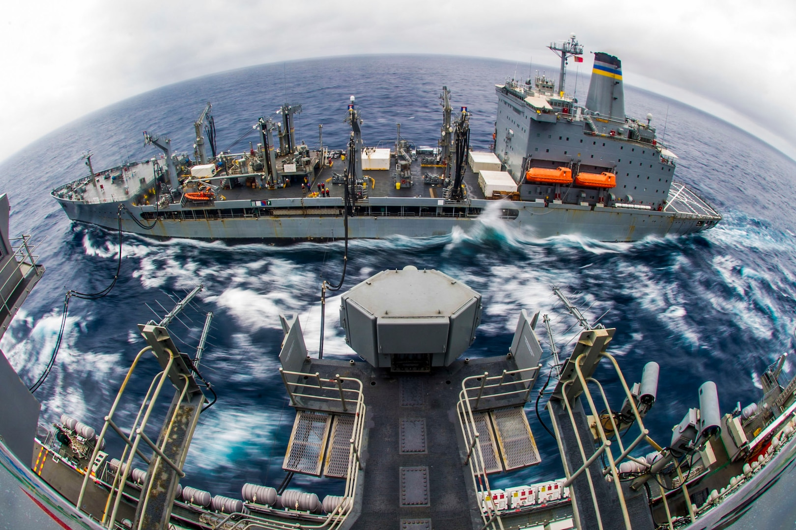 Two ships move together while one delivers fuel to the other.