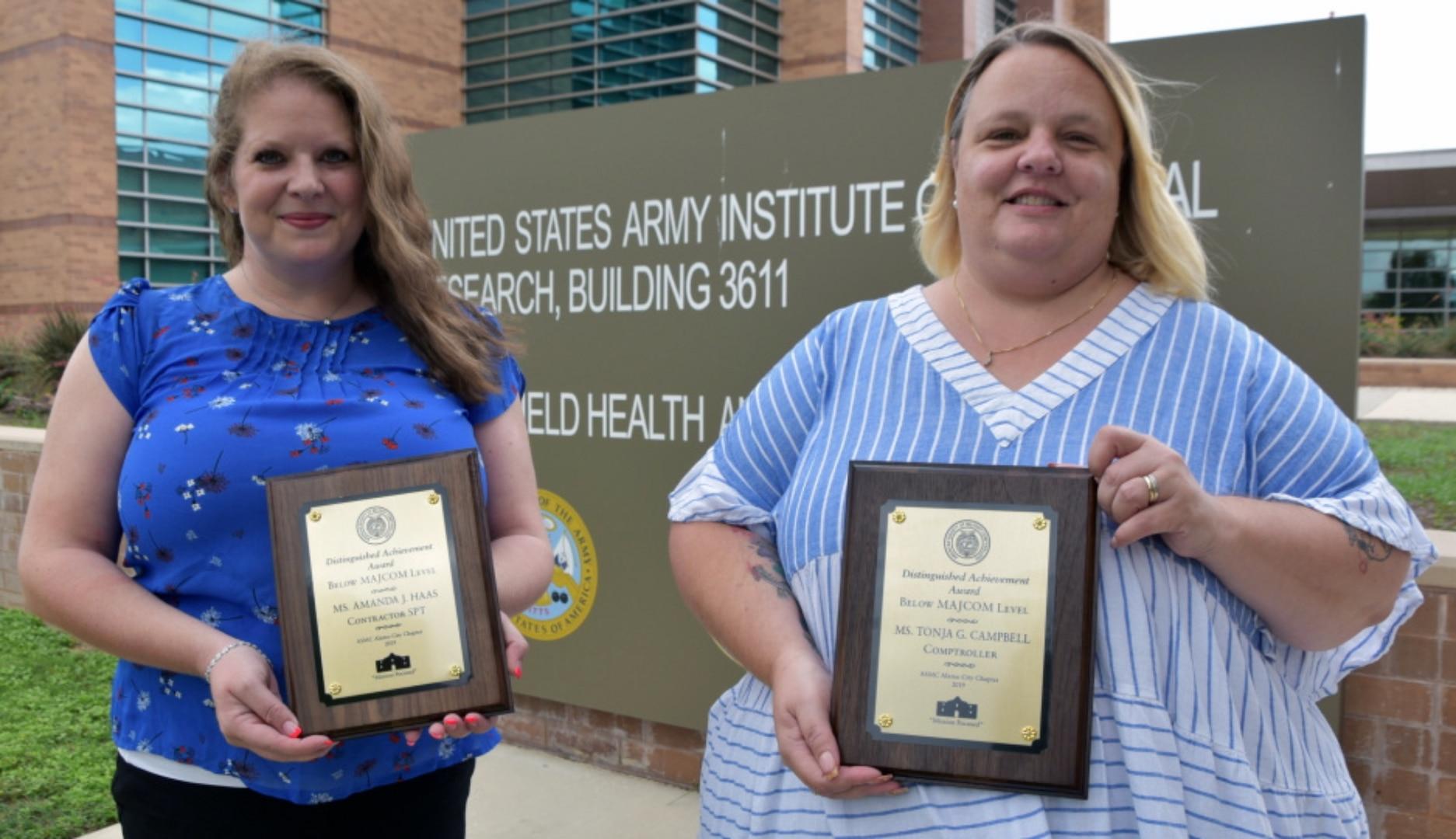 Award winners display their plaques