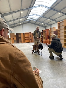 Man crouches down in front of dog being held by trainer.