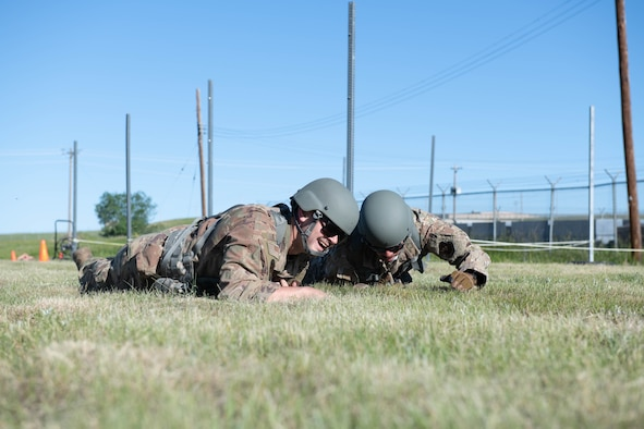 Airmen low-crawl during a battle buddy hill climb competitive event