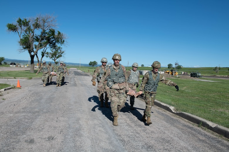 Airmen carry a manikin on a stretcher