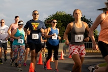 U.S. Marine Corps Col. Speros Koumparakis, commanding officer, Marine Corps Base Hawaii, his wife, and other participants of group three start the race during the annual Surf & Turf 5K, Marine Corps Base Hawaii, June 12, 2021. The annual Surf & Turf 5K aided in the resiliency of service members, their families, and our civilian employees, increasing esprit de corps. (U.S. Marine Corps photo by Lance Cpl. Terry Stennett III)