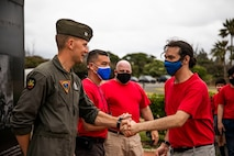 U.S. Marine Corps Capt. Matthew Desrochers, a pilot with Marine Aircraft Group 24, shakes hands with a boy scout from Troop 113 at the end of a community relations event, Marine Corps Base Hawaii, June 17, 2021. MAG 24 hosted the event in an effort to give the boy scouts an opportunity to learn about the world of military aviation. (U.S. Marine Corps photo by Lance Cpl. Brandon Aultman)