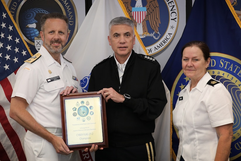 One sailor and two soldiers pose for a photo with a plaque.