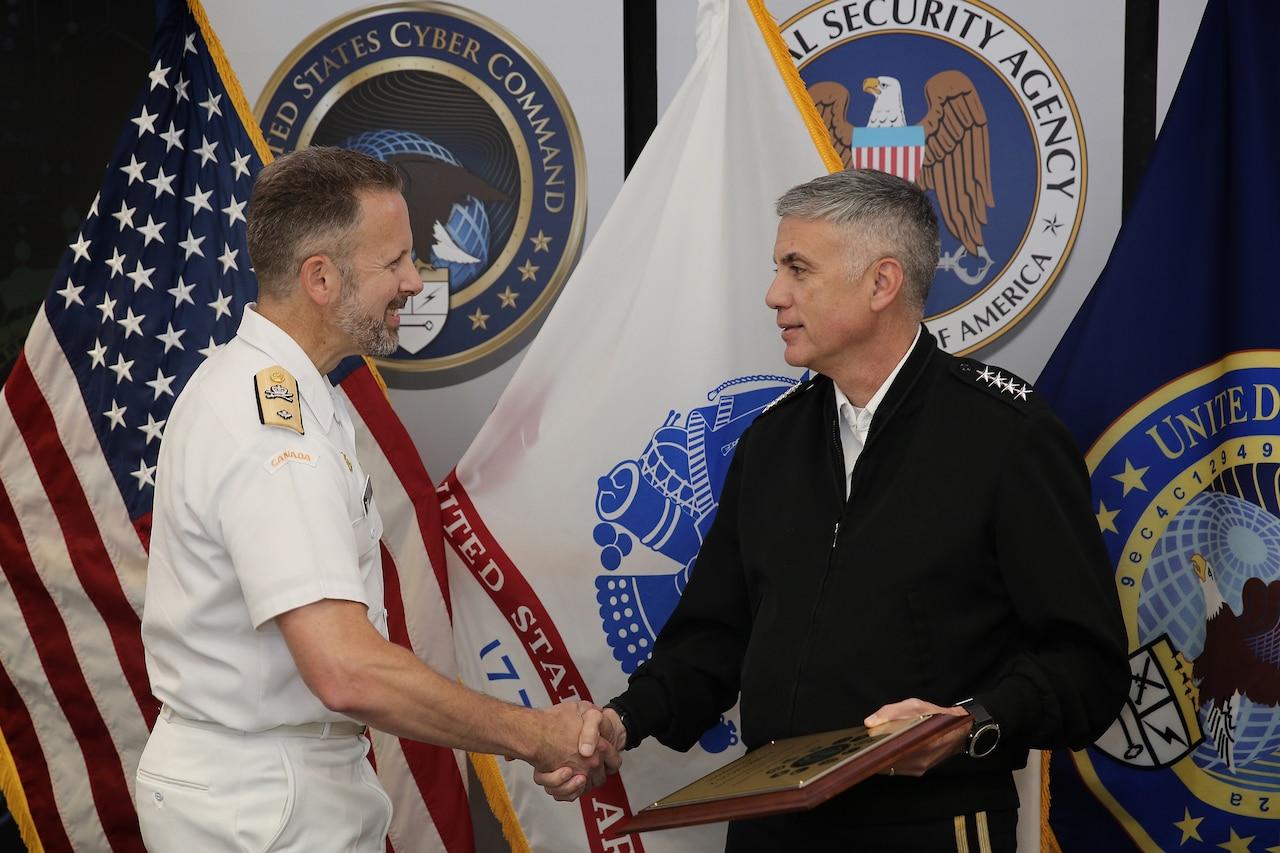 Two men wearing uniforms shake hands.