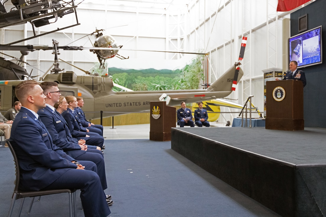 Men and women in military uniforms sit listening to a speaker on a stage