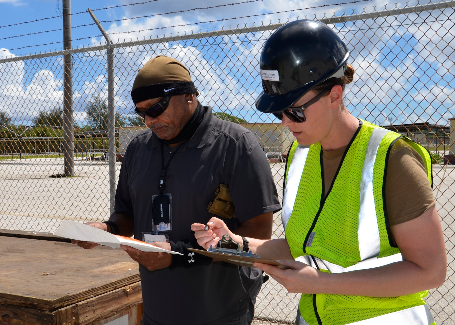 A woman and man go over a checklist in front of a fence.