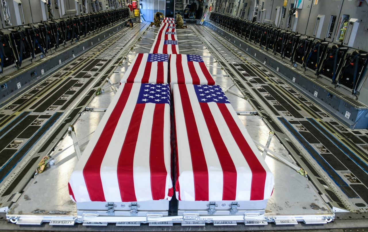 At least 10 large cases are draped with U.S. flags. In the background, two service members attach a flag to a case.