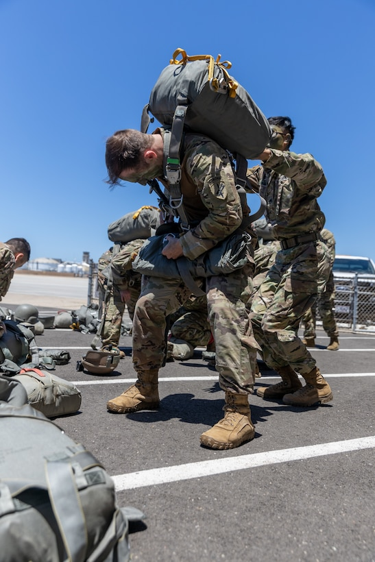 U.S. Army Soldiers with 301st Tactical Psychological Operations, PSYOP, Company (Airborne),14th PSYOP Battalion, 7th PSYOP Group, assist each other with their static-line chutes before performing pre-jump checks during a U.S. Air Force KC-130 Hercules static-line jump exercise at Naval Base Coronado, California, June 11, 2021. The 301st TCP invited I Marine Expeditionary Force Information Group PSYOP Marines to observe jump training before attending the U.S. Army Airborne school. Gaining jump qualifications enables I MIG to effectively integrate and support I Marine Expeditionary Force information operations in forward deployed environments.