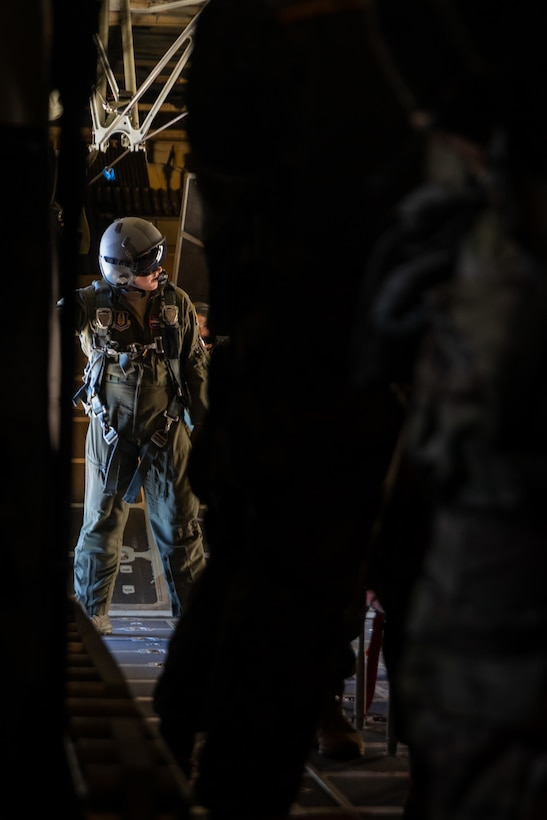 A U.S. Air Force crew chief checks for an all clear during a U.S. Air Force KC-130 Hercules static-line jump exercise at Naval Base Coronado, California, June 11, 2021. The 301st TCP invited I Marine Expeditionary Force Information Group PSYOP Marines to observe jump training before attending the U.S. Army Airborne school. Gaining jump qualifications enables I MIG to effectively integrate and support I Marine Expeditionary Force information operations in forward deployed environments.