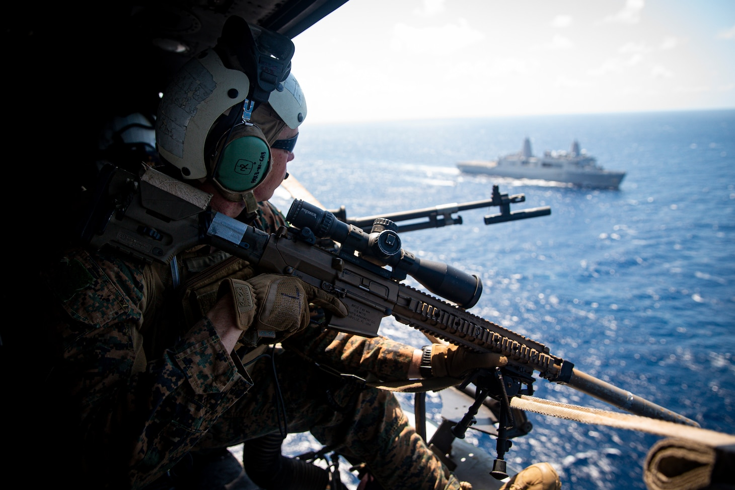 210623-M-TS451-2483 PHILIPPINE SEA - A U.S. Marine with Force Reconnaissance Platoon, 31st Marine Expeditionary Unit (MEU), observes the Philippine Sea while in route to the USS Germantown (LSD 42) to conduct a Maritime Interdiction Operation (MIO) training exercise June 24, 2021. The MIO consisted of Force Reconnaissance Marines fast roping on to the USS Germantown and executing a search and seizure scenario with support from the Battalion Landing Team 3/5 as the security element. The 31st MEU is operating aboard ships of the America Amphibious Ready Group in the 7th fleet area of operation to enhance interoperability with allies and partners and serve as a ready response force to defend peace and stability in the Indo-Pacific region. (U.S. Marine Corps photo by Cpl. Karis Mattingly)