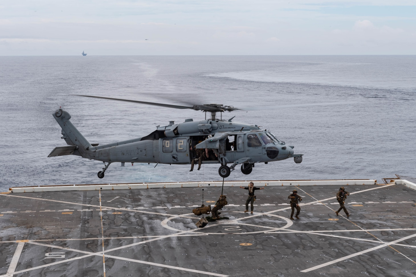 210614-N-XB010-1015 EAST CHINA SEA (June 14, 2021) Marines attached to the 31st Marine Expeditionary Unit (MEU) fast rope from a Marine Corps MH-60S: Sea Hawk from the 31st MEU on USS New Orleans's (LPD 18) flight deck during a Maritime Raid Force training evolution with USS Germantown (LSD 42). New Orleans, part of the America Amphibious Ready Group, along with the 31st Marine Expeditionary Unit, is operating in the U.S. 7th Fleet area of responsibility to enhance interoperability with allies and partners and serve as a ready response force to defend peace and stability in the Indo-Pacific region. (U.S. Navy photo by Mass Communication Specialist 2nd Class Desmond Parks)