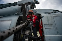 """Aviation Ordnanceman 3rd Class Samuel Garcia, from Berwyn, Illinois, prepares a .50-caliber gun mount on an MH-60R Sea Hawk helicopter, attached to the """"Proud Warriors"""" of Helicopter Maritime Strike Squadron (HSM) 72, on the flight deck of the Nimitz-class aircraft carrier USS Harry S. Truman (CVN 75) during Group Sail."""