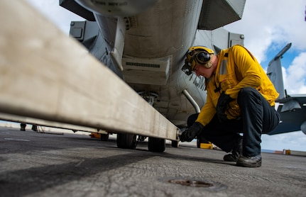 """Aviation Boatswain's Mate (Handling) 1st Class Jeffrey Hayes, from Aurora, Colorado, checks a fastener on a tow arm beneath an MH-60R Seahawk helicopter, attached to the """"Pround Warriors"""" of Helicopter Maritime Strike Squadron (HSM) 72, on the flight deck of the Nimitz-class aircraft carrier USS Harry S. Truman (CVN 75) during Group Sail."""