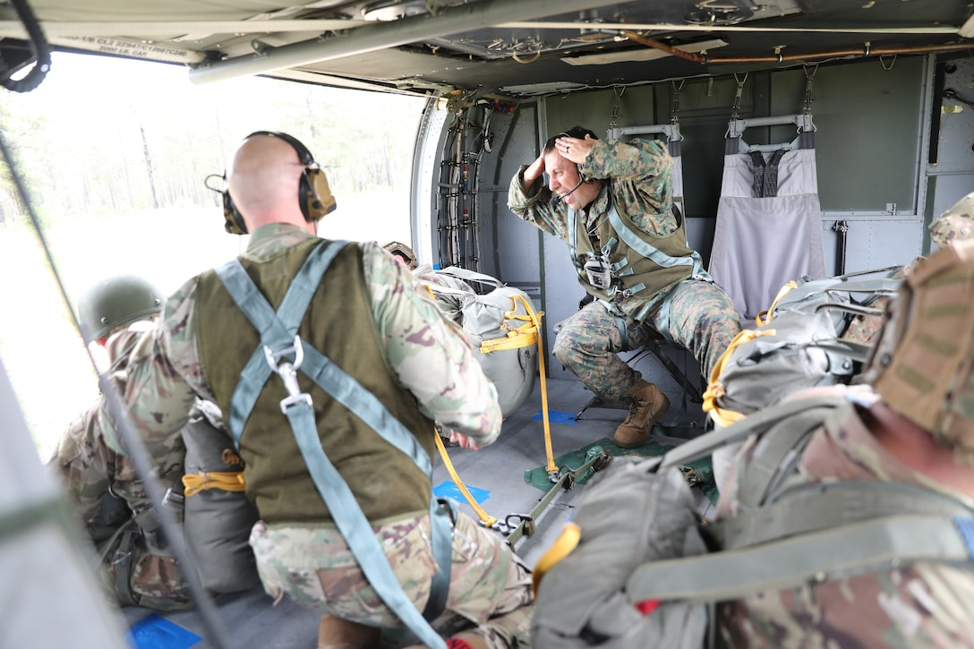 U.S. Army Reserve Lt. Col. Stephen M. Cowne, Jr., G33 and jumpmaster for the U.S. Army Civil Affairs and Psychological Operations Command (Airborne), watches as Capt. Ignacio Rios, a Chilean jumpmaster assigned to the 1st Special Warfare Training Group(A), U.S. Army John F. Kennedy Special Warfare Center and School (USAJFKSWCS) signal in preparation for nontactical airborne operations, June 5, 2021, at Saint Mere Eglise drop zone, Fort Bragg, N.C. Paratroopers jumping during the airborne operations were eligible to earn foreign wings.