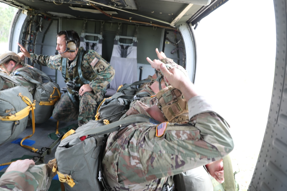 U.S. Army Reserve paratroopers prepare for nontactical airborne operations, June 5, 2021, at Saint Mere Eglise drop zone, Fort Bragg, N.C. USACAPOC(A) jumpmasters worked with Capt. Ignacio Rios, a Chilean jumpmaster assigned to the 1st Special Warfare Training Group(A), U.S. Army John F. Kennedy Special Warfare Center and School (USAJFKSWCS). Paratroopers jumping during the airborne operations were eligible to earn foreign wings.