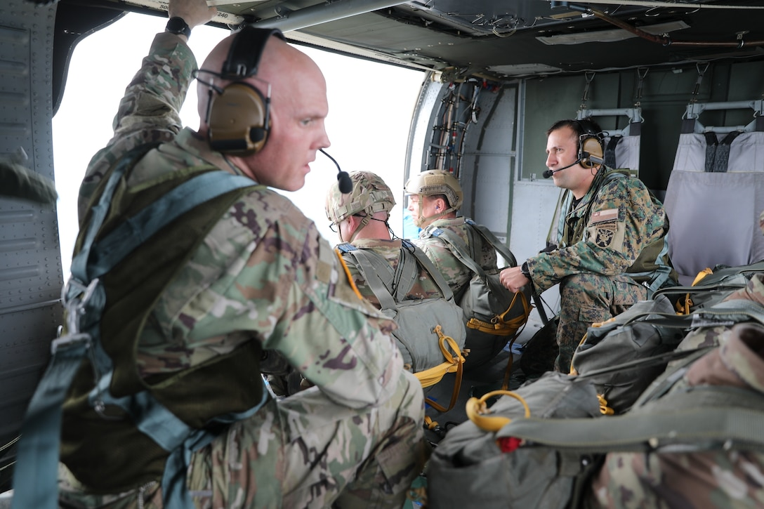 U.S. Army Reserve Lt. Col. Stephen M. Cowne, Jr., G33 and jumpmaster for the U.S. Army Civil Affairs and Psychological Operations Command (Airborne), and Capt. Ignacio Rios, a Chilean jumpmaster assigned to the 1st Special Warfare Training Group(A), U.S. Army John F. Kennedy Special Warfare Center and School (USAJFKSWCS) prepare for nontactical airborne operations, June 5, 2021, at Saint Mere Eglise drop zone, Fort Bragg, N.C. Paratroopers jumping during the airborne operations were eligible to earn foreign wings.