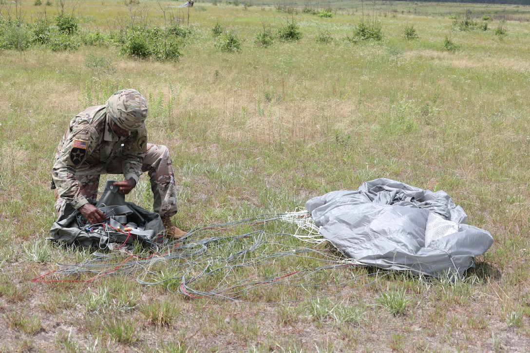 U.S. Army Reserve Master Sgt. Folarin L. Durosawo, assistant Inspector General for the U.S. Army Civil Affairs and Psychological Operations Command (Airborne), collects his parachute to bring back to a consolidated collection point during nontactical airborne operations at Saint Mere Eglise drop zone, Fort Bragg, N.C., June 5, 2021. USACAPOC(A) jumpmasters worked with Capt. Ignacio Rios, a Chilean jumpmaster assigned to the 1st Special Warfare Training Group(A), U.S. Army John F. Kennedy Special Warfare Center and School (USAJFKSWCS). Paratroopers jumping during the airborne operations were eligible to earn foreign wings.