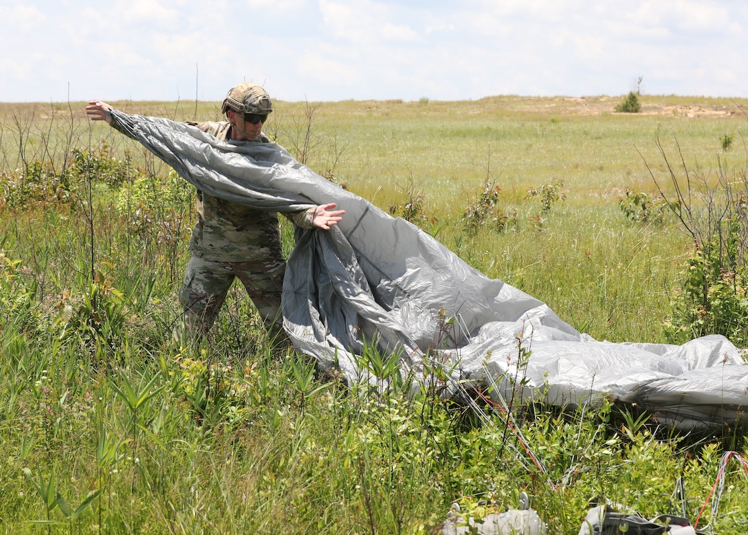U.S. Army Reserve Maj. Paul F. Arentz, staff judge advocate with the U.S. Army Civil Affairs and Psychological Operations Command (Airborne), collects his parachute to bring back to a consolidated collection point during nontactical airborne operations at Saint Mere Eglise drop zone, Fort Bragg, N.C., June 5, 2021. USACAPOC(A) jumpmasters worked with Capt. Ignacio Rios, a Chilean jumpmaster assigned to the 1st Special Warfare Training Group(A), U.S. Army John F. Kennedy Special Warfare Center and School (USAJFKSWCS). Paratroopers jumping during the airborne operations were eligible to earn foreign wings.