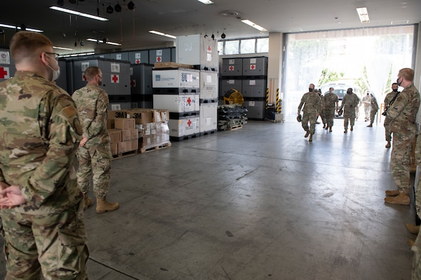 Maj. Gen. Michael Place, 18th Medical Command (Deployment Support) commanding general, center, enters into the War Reserve Materiel warehouse at Yokota Air Base, Japan, June 24, 2021. During a tour of the base, Place visited both the WRM warehouse and Patient Movement Inventory Center to gain a better understanding of how Yokota Air Base could utilize its resources in a joint deployed environment. (U.S. Air Force photo by Staff Sgt. Joshua Edwards)