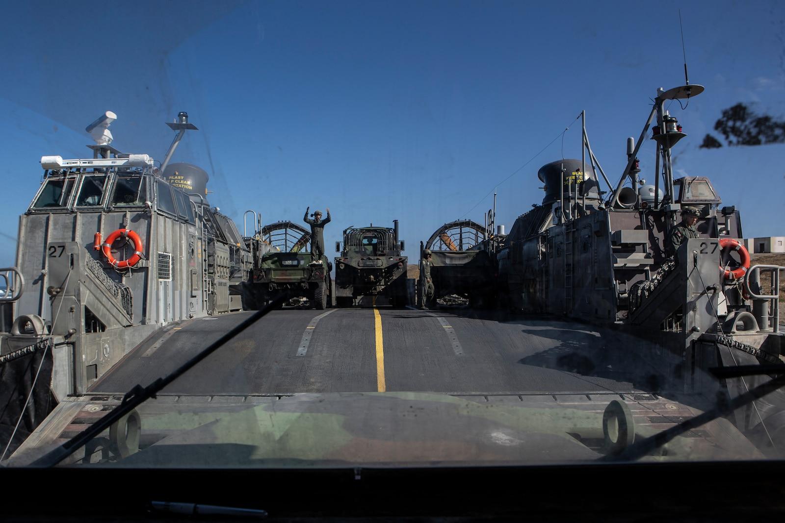 A U.S. Sailor, with Assault Craft Unit (ACU) 5, guides a convoy.