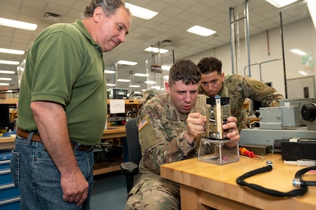 Photo of Electronics Mechanic Leader overseeing Soldiers during a side-by-side training effort.