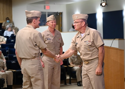 Rear Adm. Curt Copley (center) assumed command of the Office of Naval Intelligence and directorship of the National Maritime Intelligence-Integration Office during a ceremony June 18 at the National Maritime Intelligence Center in Suitland, Md. Deputy Chief of Naval Operations for Information Warfare and Director of Naval Intelligence Vice Adm. Jeffrey Trussler (right), the guest speaker, congratulates Rear Adm. Price (left) for taking the helm for the second time and seamlessly leading the organizations through another leadership transition.