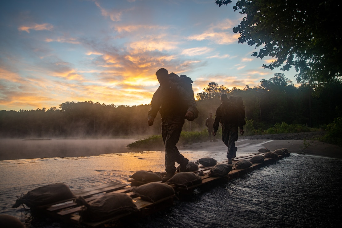 U.S. Marine Corps Capt. Thomas White, left, and Capt. Devon Sanderfield, both infantry officers with 2d Marine Division (MARDIV), cross a creek during a 20 km hike as part of the Division Leader Assessment Program (DLAP) at Fort Pickett, Va., June 24, 2021. DLAP assesses the preparedness of 2d MARDIV's newly-assigned infantry Captains by evaluating their mental, moral, and physical readiness for infantry company command, ensuring the Division places the right leaders in front of the right companies at the right time. DLAP is a key component in the Division's mission to train and certify units that demonstrate apex levels of lethality, endurance and comprehensive warfighting ability to be employed by their gaining higher headquarters immediately upon deployment. (U.S. Marine Corps photo by Lance Cpl. Brian Bolin Jr.)