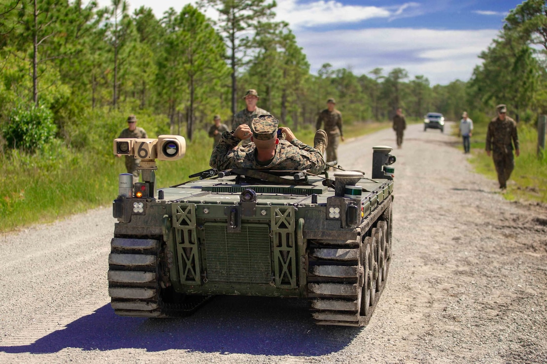U.S. Marines with 1st Battalion, 2d Marine Regiment (1/2), 2d Marine Division, rehearse medical evacuation scenarios with an Expeditionary Modular Autonomous Vehicle (EMAV) during a training event on Camp Lejeune, N.C., June 24, 2021. The purpose of this training is to provide electronic warfare services to a supported unit commander. The EMAV is a highly mobile and fully autonomous ground vehicle that has a payload capacity of 7,200 pounds. (U.S. Marine Corps photo by Lance Cpl. Emma L. Gray)