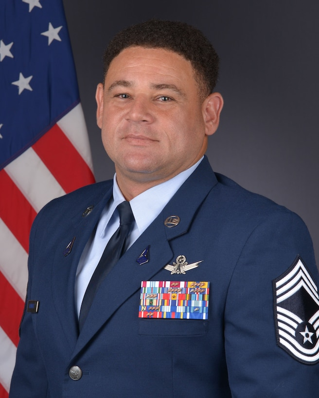 CMSgt Omar Basnight poses in front of the American Flag for his official photo.