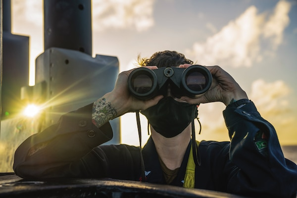 Logistics Specialist (Submarine) 1st Class Anna Donelan, assigned to Gold crew of Ohio-class guided-missile submarine USS Ohio, scans for contacts while standing lookout watch on bridge, Pacific Ocean, January 22, 2021 (U.S. Navy/Kelsey J. Hockenberger)