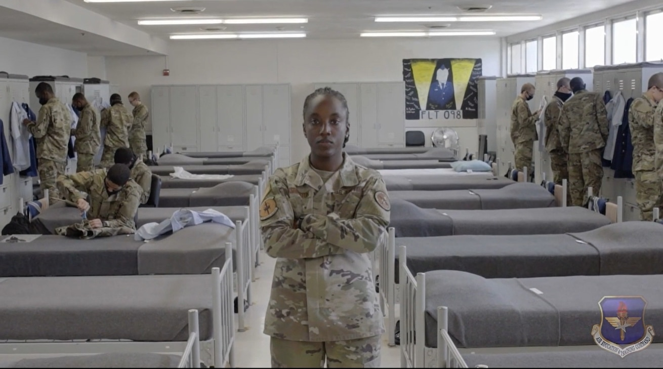 Staff Sgt. Alexandria Washington stands with her arms crossed while trainees are at their lockers in the background.