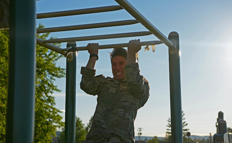 U.S. Air Force Airman 1st Class Michael Flores, a 354th Security Forces Squadron installation entry controller, does a pull-up during a special weapons and tactics (SWAT) physical training test June 23, 2021 on Eielson Air Force Base, Alaska. A physical training test challenged defenders to meet the demanding standard of SWAT training.(U.S. Air Force photo by Senior Airman Beaux Hebert)