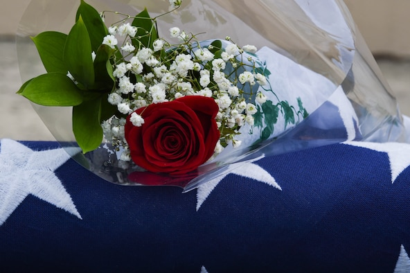 A rose and flag sit on an empty seat during a memorial ceremony