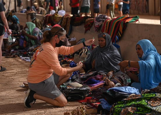 A U.S. service member assigned to Nigerien Air Base 201 browses through a vendor's inventory during a bazaar at the base in Agadez, Niger, June 20, 2021. Members of Air Base 201 successfully injected more than 4.2 million West African CFA Franc which is approximately 14 thousand dollars into the local economy.(U.S. Air Force photo by Airman 1st Class Jan K. Valle)