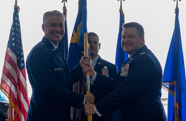 U.S. Air Force Brig. Gen. Jeremy Sloane, 36th Wing commander, passes the 6th Mission Support Group guidon to U.S. Air Force Col. Kenneth Herndon, 36th MSG incoming commander, during a change of command ceremony at Andersen Air Force Base, Guam, June 29, 2021.